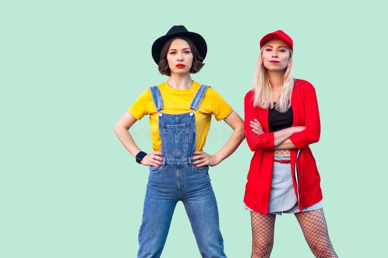 Couples de beaux meilleurs amis sérieux de hippie de stilysh dans des vêtements à la mode se tenant, posant avec les visages fier images stock