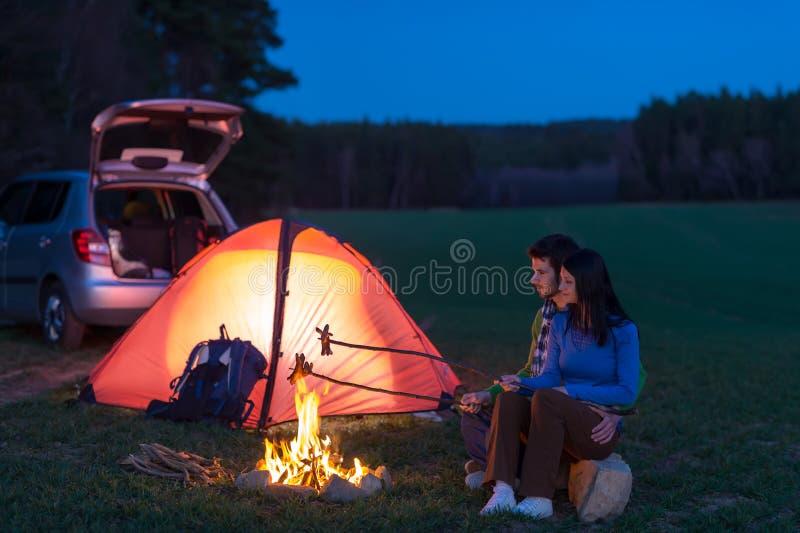Couples de camping-car de tente se reposant par le feu images libres de droits