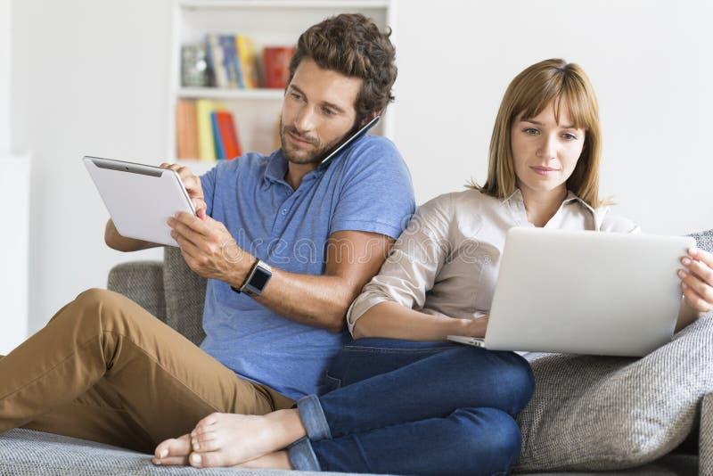 Couples de connaisseur de Digital Téléphone portable, smartwatch, comprimé, ordinateur portable Appartement blanc moderne image stock