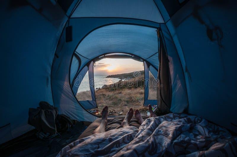 Couples de déplacement de matin dans une tente par la mer, vue de la première personne image stock