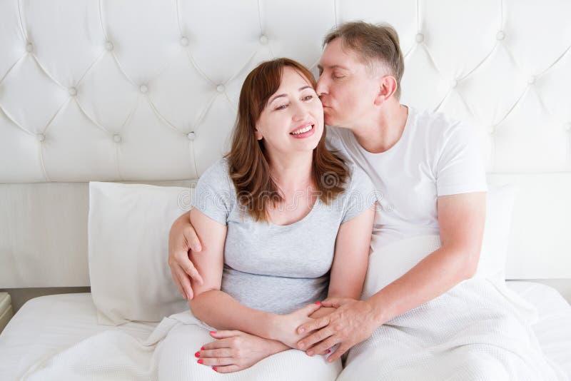 Couples de famille de Moyen Âge dans la chambre à coucher blanche dans le lit Épouse de baiser de mari Amour et romance Rapport s images stock