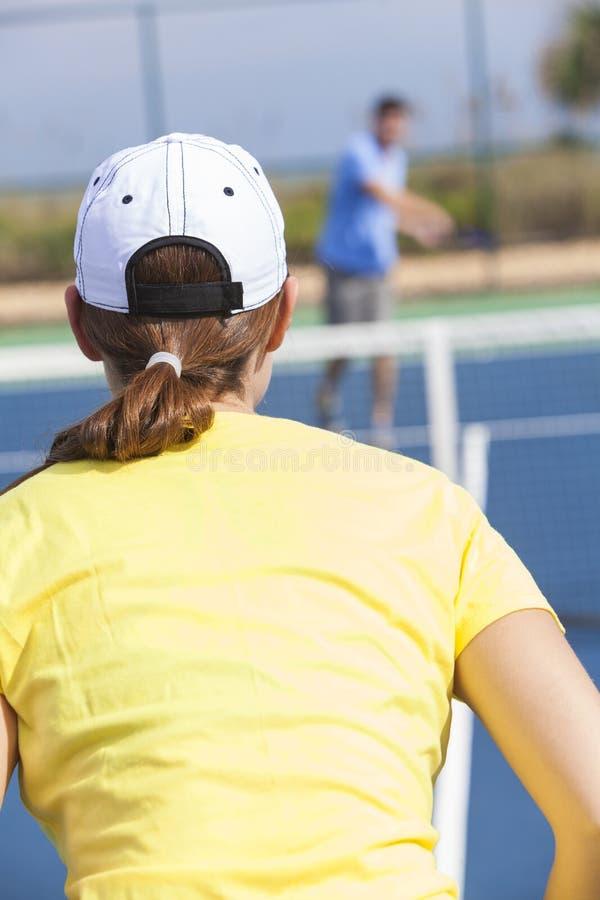 Couples de femme d'homme jouant le tennis ou la leçon photos stock