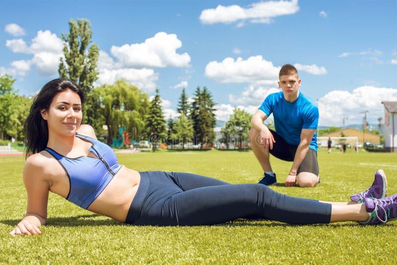 Couples de forme physique détendant après la formation sur l'herbe photos libres de droits