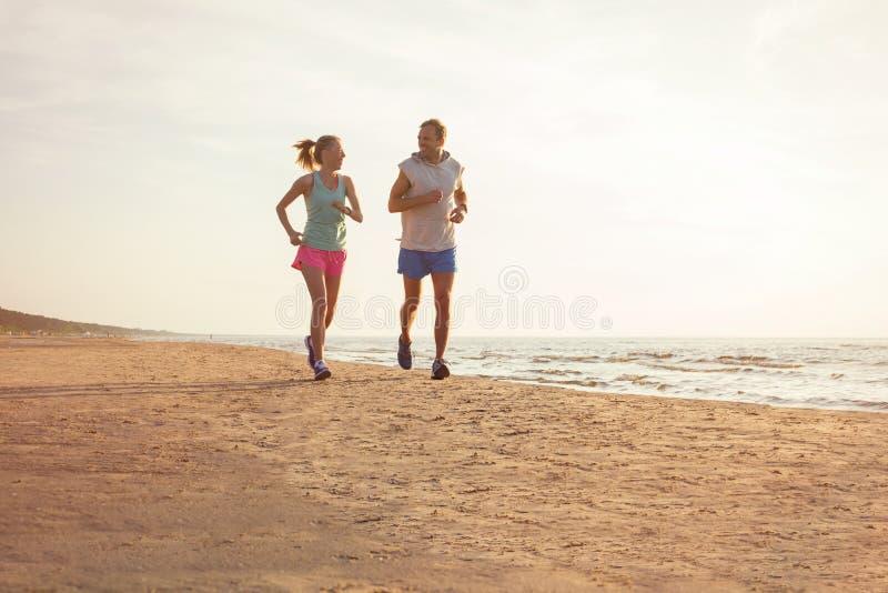 Couples de forme physique fonctionnant sur la plage images libres de droits