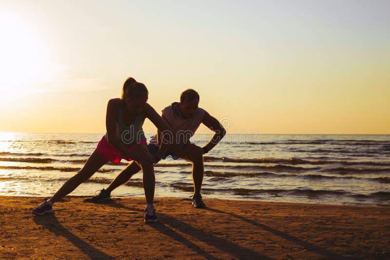 Couples de forme physique s'étendant dans le coucher du soleil images libres de droits