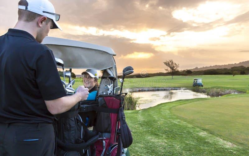 Couples de golf mettant sur le vert image libre de droits