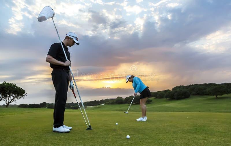 Couples de golf mettant sur le vert photographie stock
