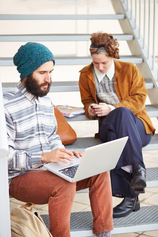 Couples de hippie utilisant l'ordinateur et le smartphone dehors photos stock