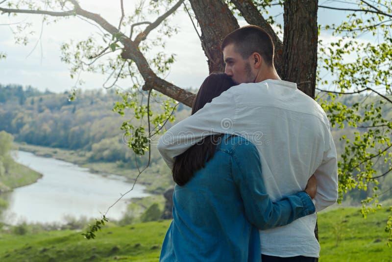 Couples de jeune beaux homme et de femme étreignant dehors au jour d'été ensoleillé images stock