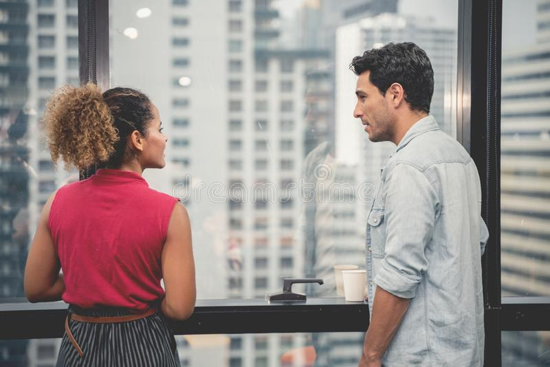 Couples de jeunes concepteurs travaillant au bureau moderne, deux coll?gues discutant le projet d'amusement au-dessus d'un ordina photo stock