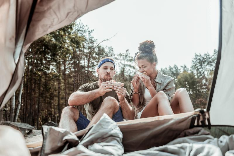 Couples de jeunes randonneurs appréciant le goût des sandwichs végétaux après longue journée images stock