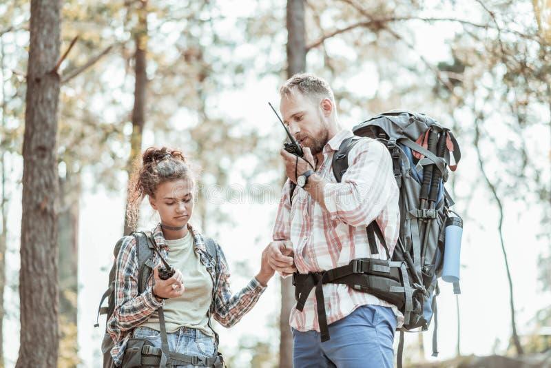 Couples de jeunes randonneurs employant leurs bipeurs après avoir été perdu dans la forêt photos libres de droits