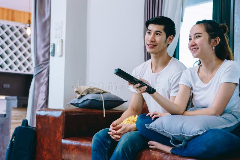 Couples de l'adolescence asiatiques regardant la TV ensemble heureusement photographie stock