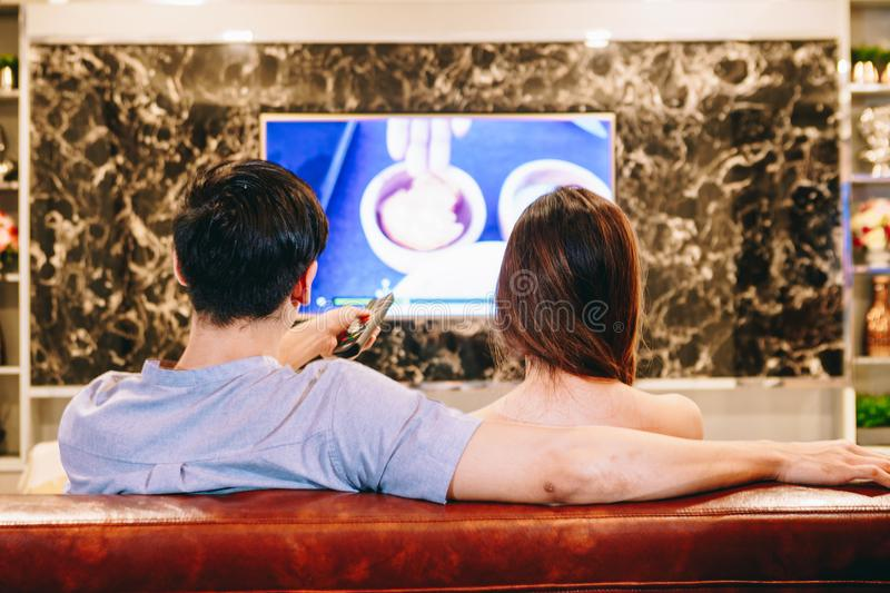 Couples de l'adolescence asiatiques regardant la TV ensemble heureusement photo stock