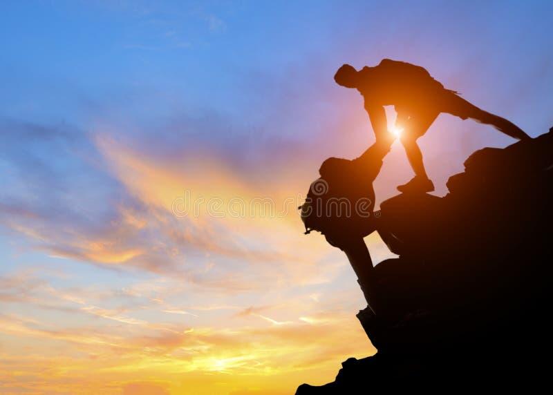 Couples de l'Asie augmentant l'aide silhouette en montagnes photos stock