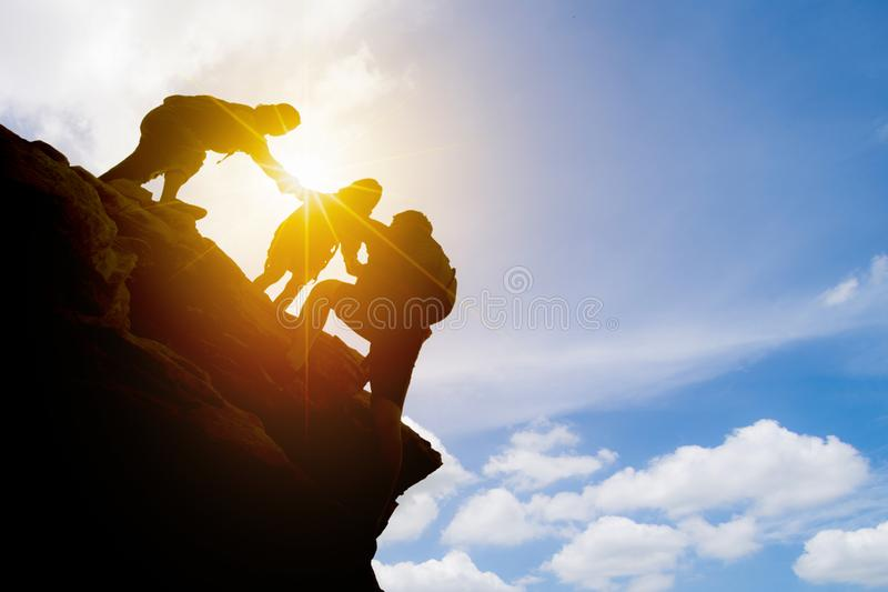 Couples de l'Asie augmentant l'aide silhouette en montagnes avec la lumière du soleil couples augmentant l'aide silhouette en mon image stock