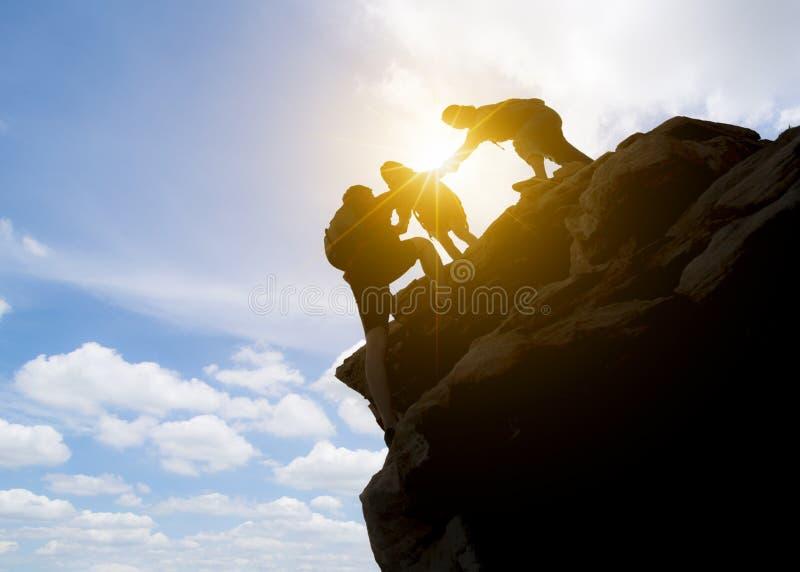 Couples de l'Asie augmentant l'aide silhouette en montagnes avec la lumière du soleil couples augmentant l'aide silhouette en mon images stock