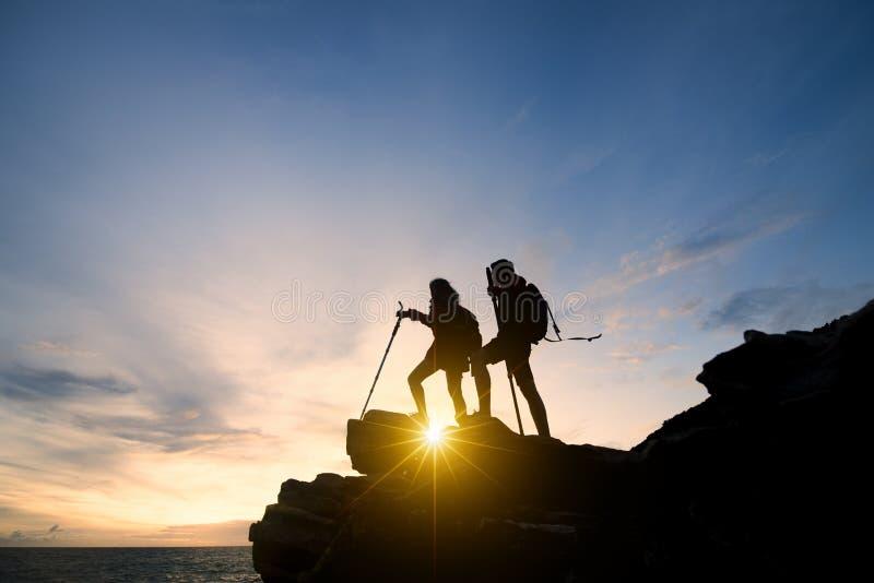 Couples de l'Asie augmentant l'aide silhouette en montagnes avec la lumière du soleil couples augmentant l'aide silhouette en mon photo stock