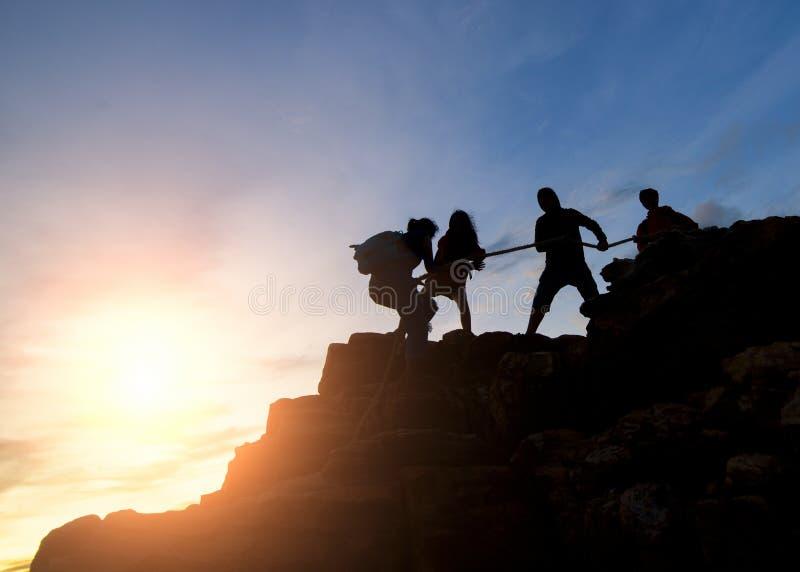 Couples de l'Asie augmentant l'aide silhouette en montagnes avec la lumière du soleil, couple augmentant l'aide silhouette dans d photo stock