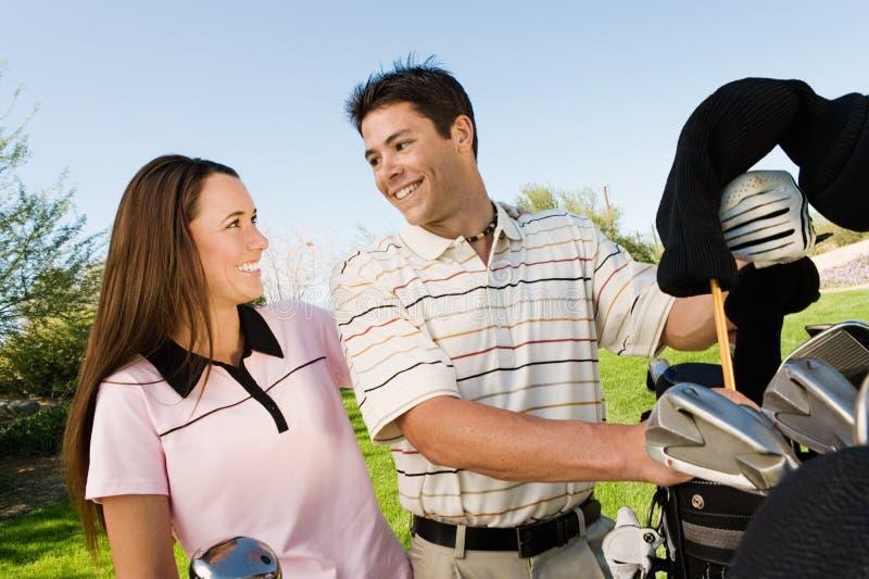 Couples de la causerie de golfeurs image libre de droits