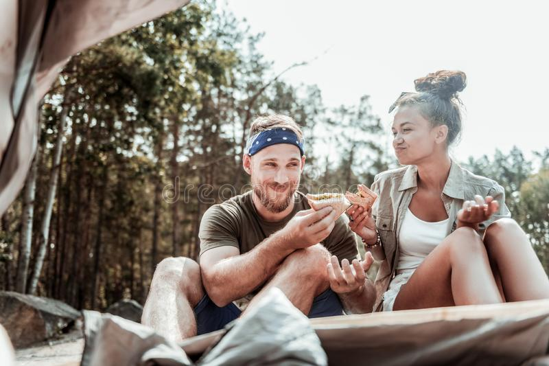 Couples de lancement de jeunes voyageurs mangeant les sandwichs savoureux avec de la laitue près de la tente images stock