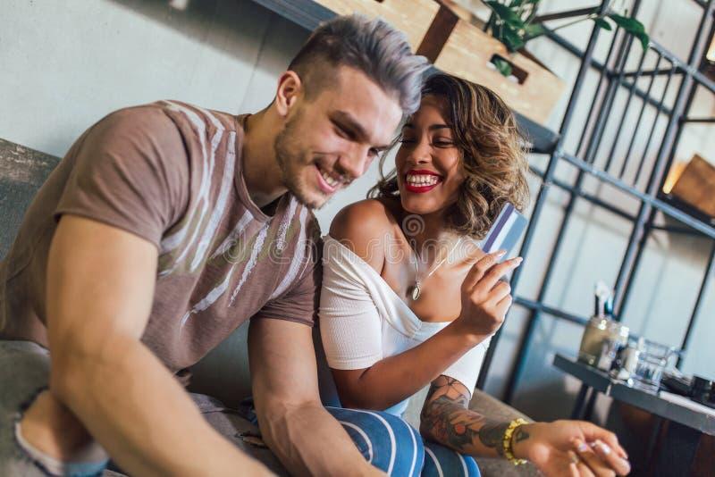 Couples de métis achetant en ligne avec la carte de crédit et l'ordinateur portable image stock
