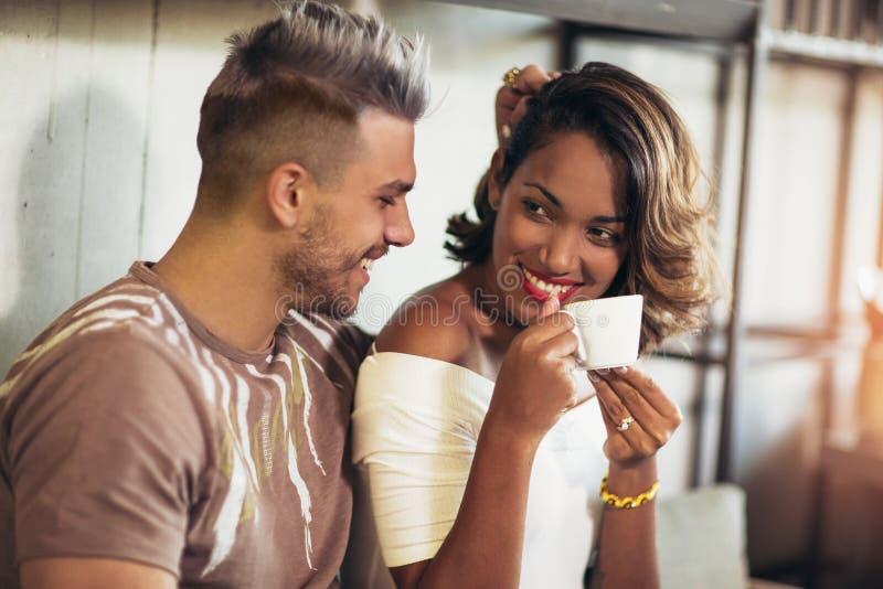 Couples de métis ayant l'amusement au café photo libre de droits