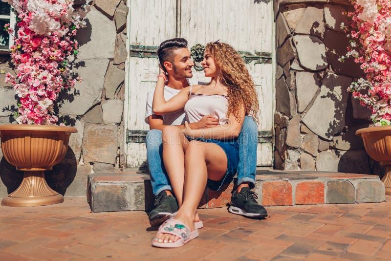 Couples de métis dans l'amour étreignant se reposer par la porte de café dehors Homme arabe et femme blanche marchant dans la vil image stock