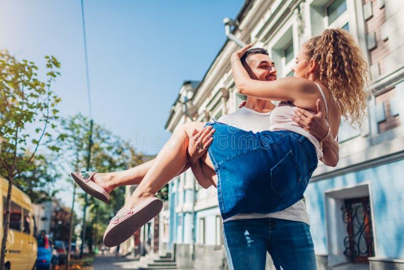 Couples de métis dans l'amour marchant dans la ville Homme arabe tenant son amie dans des mains étreindre des jeunes de gens image stock