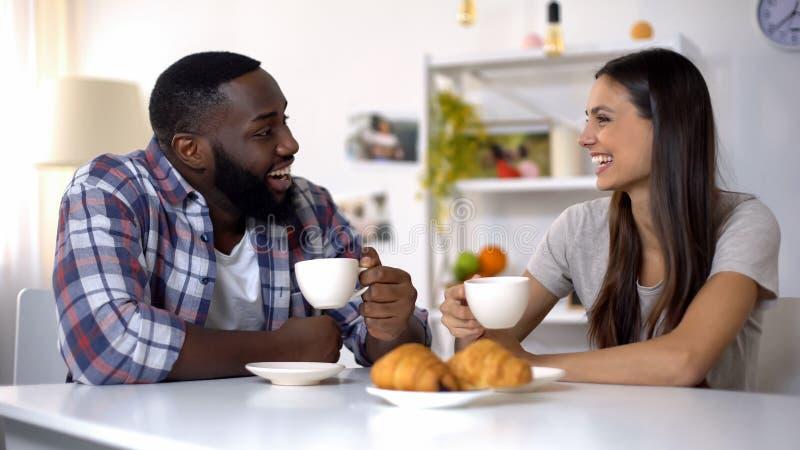 Couples de métis parlant et riant pendant le petit déjeuner à la maison, café de matin photographie stock