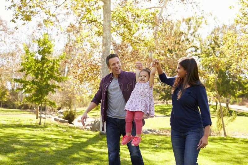 Couples de métis se soulevant vers le haut de leur jeune fille en parc photographie stock libre de droits