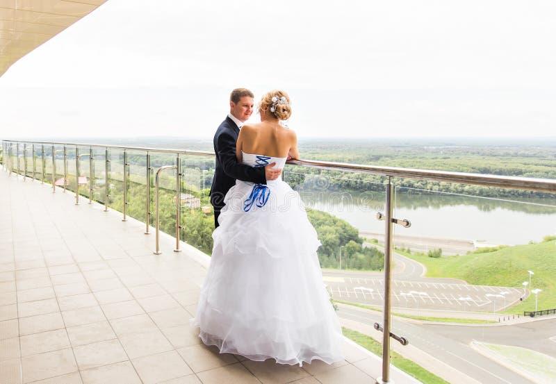 Couples de mariage étreignant, la jeune mariée tenant un bouquet des fleurs, marié l'embrassant dehors photo stock