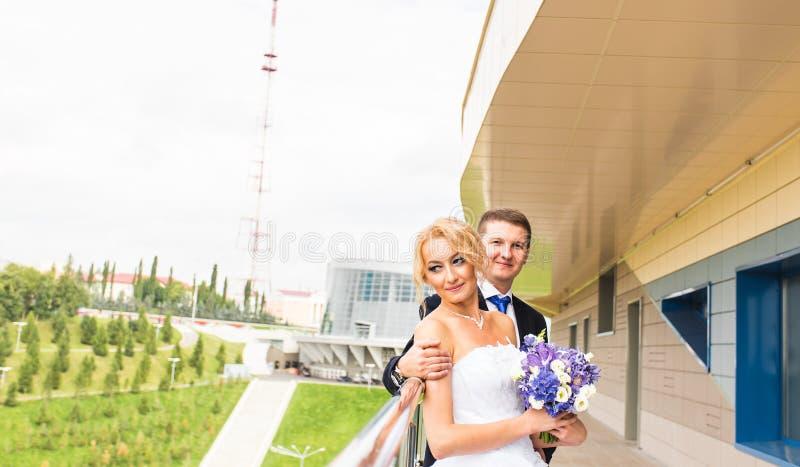 Couples de mariage étreignant, la jeune mariée tenant un bouquet des fleurs, marié l'embrassant dehors image libre de droits