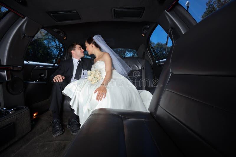 Couples de mariage dans la limousine photographie stock libre de droits