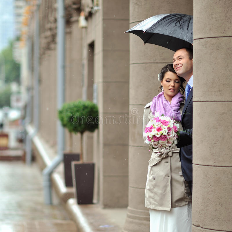 Couples de mariage dans un jour pluvieux se cachant de la pluie photographie stock libre de droits