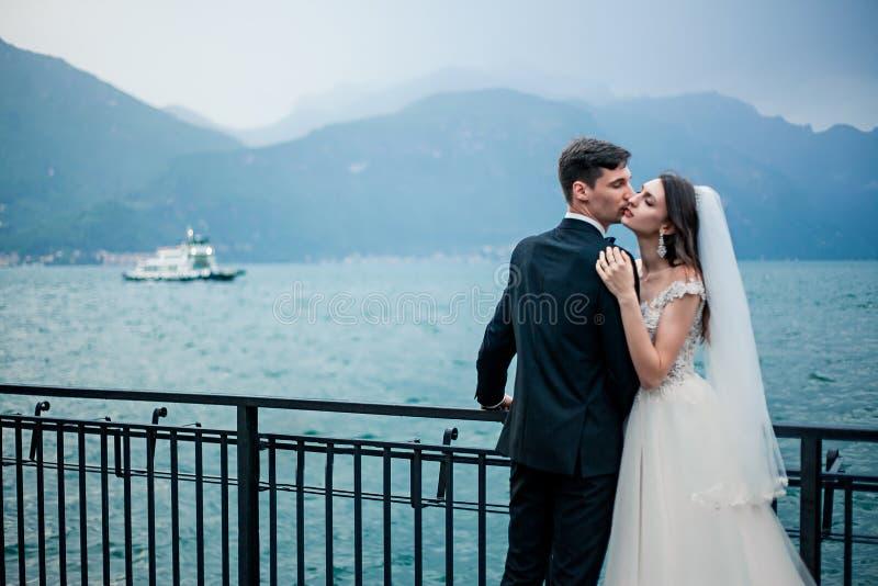Couples de mariage embrassant sur le fond d'un lac et des montagnes photographie stock libre de droits