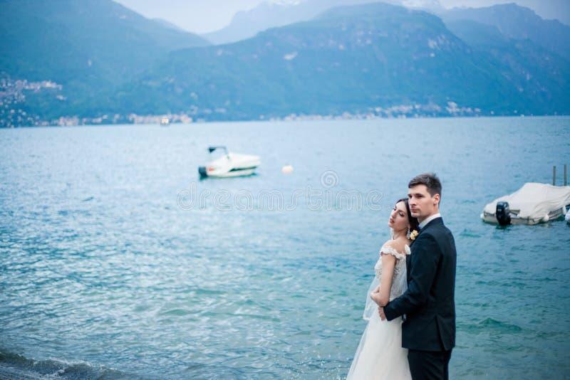 Couples de mariage embrassant sur le fond d'un lac et des montagnes photo libre de droits