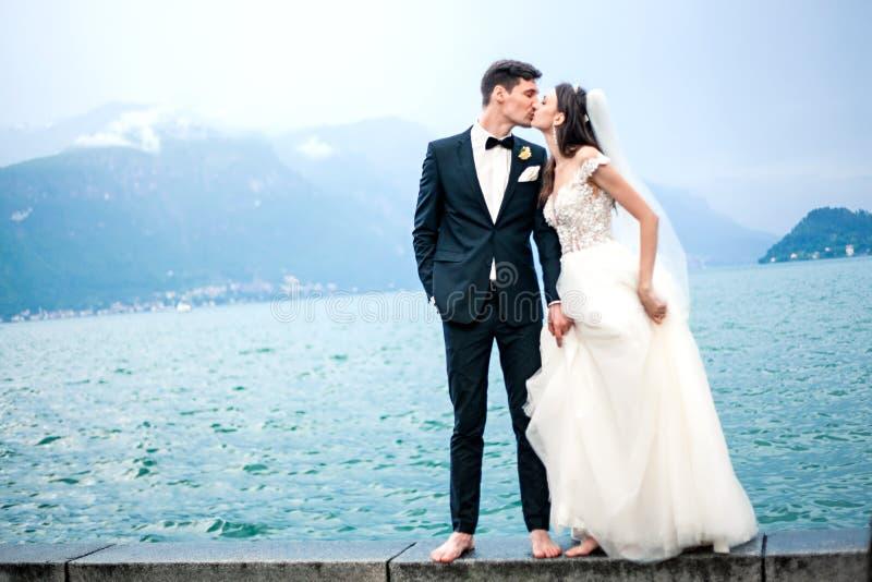 Couples de mariage embrassant sur le fond d'un lac et des montagnes images stock
