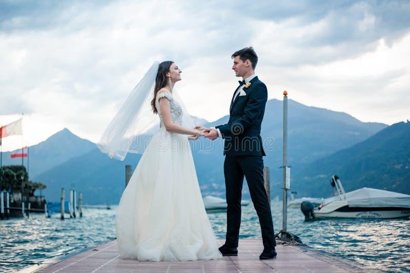 Couples de mariage embrassant sur le fond d'un lac et des montagnes photographie stock