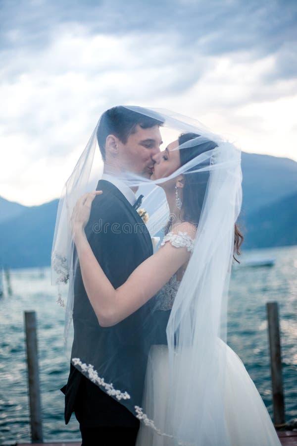 Couples de mariage embrassant sur le fond d'un lac et des montagnes photos stock