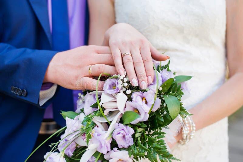 Couples de mariage mains et anneaux sur le bouquet de la jeune mariée Déclaration de l'amour Épouser le fond, détails de jour photographie stock libre de droits