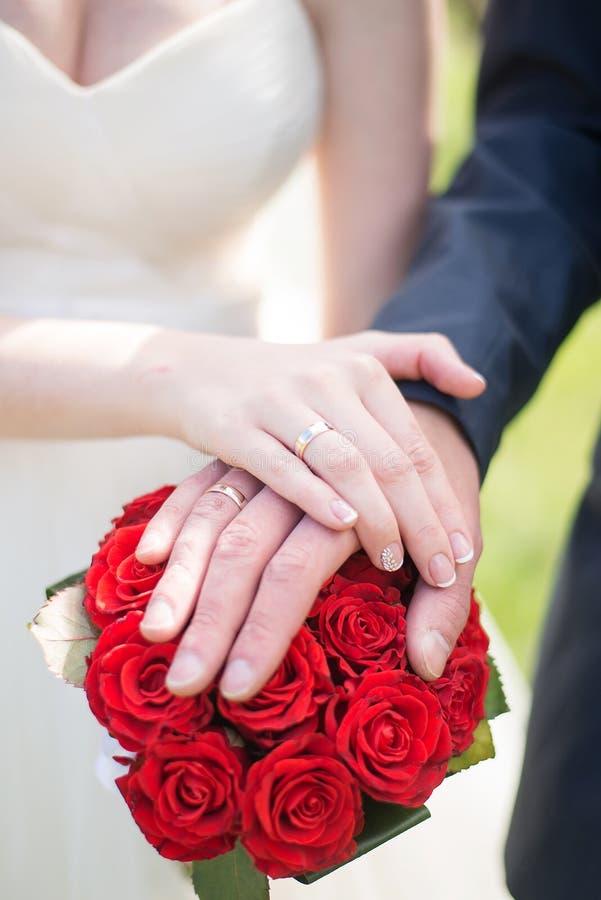 Couples de mariage mains et anneaux sur le bouquet de la jeune mariée Déclaration de l'amour Épouser le fond, détails de jour photos stock