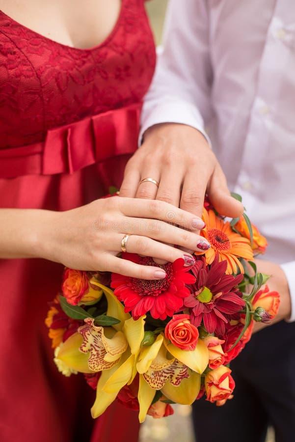 Couples de mariage mains et anneaux sur le bouquet de la jeune mariée Déclaration de l'amour Fond de mariage images libres de droits