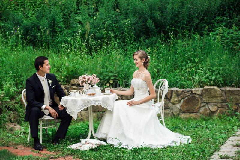 Couples de mariage se reposant à la table ayant le thé images libres de droits