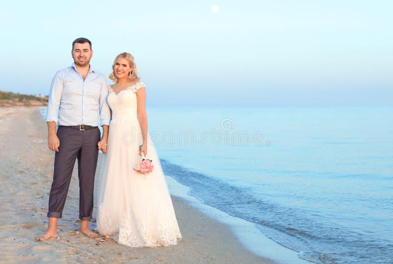 Couples de mariage se tenant sur la plage photo stock