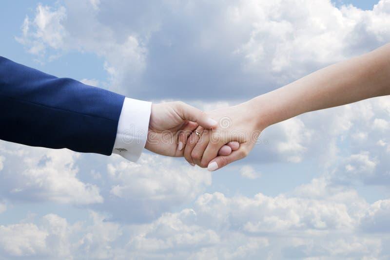 Couples de mariage tenant des mains sur le ciel bleu avec des nuages image libre de droits