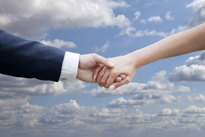 Couples de mariage tenant des mains sur le ciel bleu avec des nuages images libres de droits