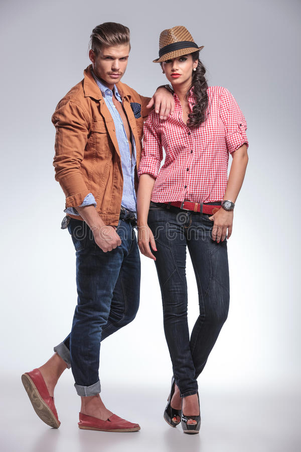 Couples de mode posant sur le fond gris de studio photo libre de droits