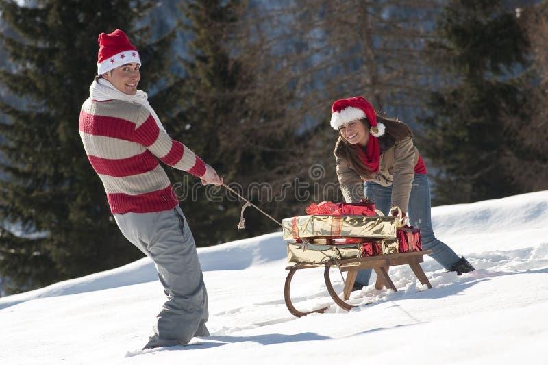 Couples De Noël Jouant Avec Des Cadeaux Dans La Neige Photographie stock