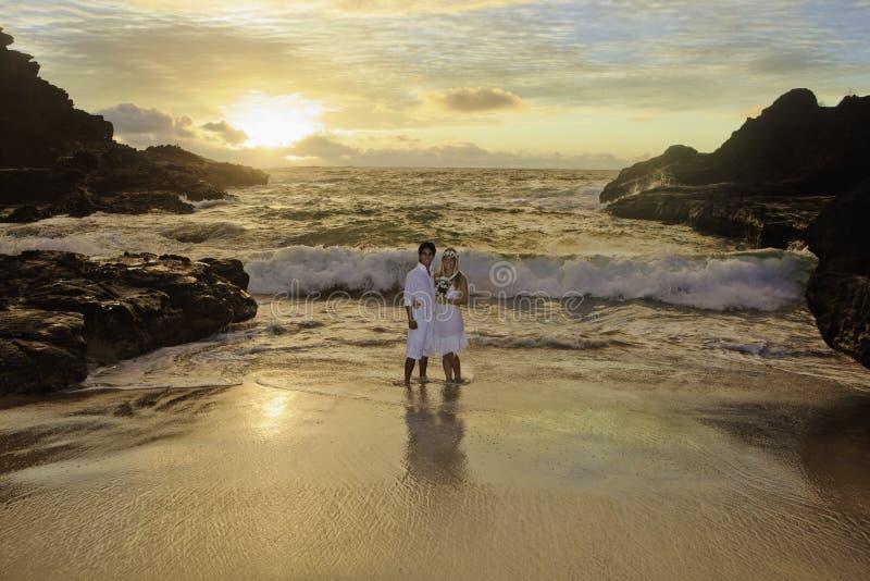 Couples de nouveaux mariés au lever de soleil photographie stock libre de droits